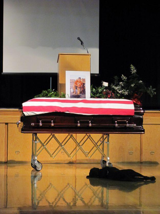 Um cão sofre de luto no funeral do seu dono, um oficial da tropa de elite da Marinha dos Estados Unidos.