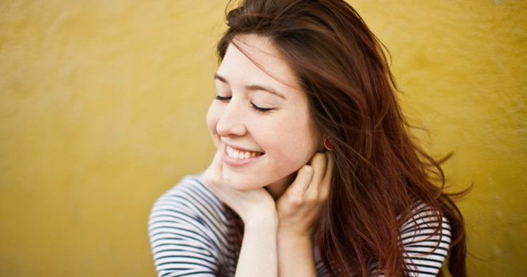 Candid portrait of young woman with eyes closed