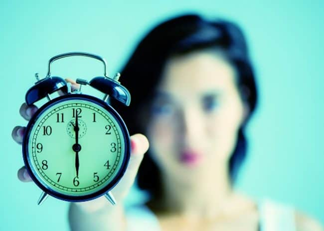 cute asian woman who is holding a clock