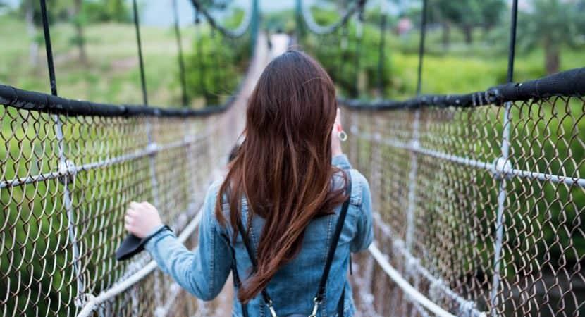 woman in blue long sleeved dress on rope bridge 1031391